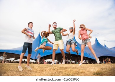 Teenagers at summer music festival dancing and jumping