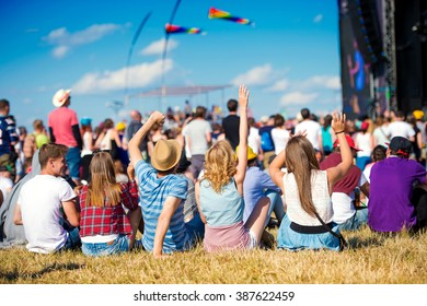 Teenagers, summer music festival, sitting in front of stage - Shutterstock ID 387622459