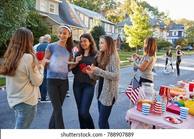 Teenagers talking in the street at a block party
