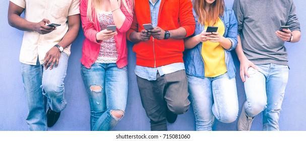 Teenager, die auf urbanen Mauern SMS schreiben - Gruppe multiethnischer Freunde, die im Freien im Handy stehen - Konzept der Studierenden, die nach sozialen Netzwerken und Telefontechnologie suchen