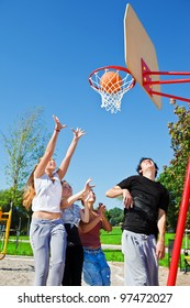 Teenagers throwing ball to the basketball hoop