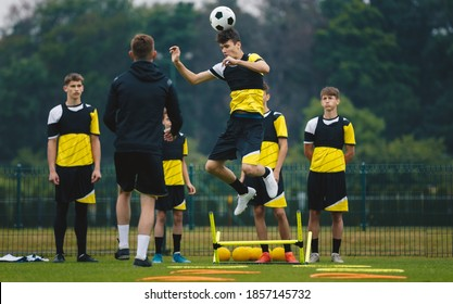 Teenagers training soccer headshot. Young player jumping high and head ball. Coach coaching junior youth football club. Team waiting in line in the background.