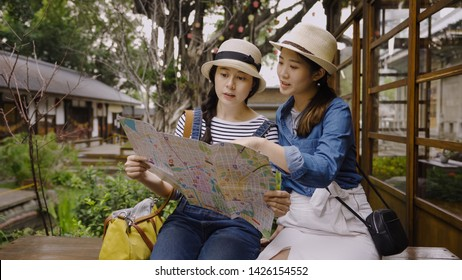 Teenagers travel kyoto japan concept. two female friends with paper map sitting on bench outdoor in teien garden japanese old town. young girls friends pointing discussing tourist attraction on guide