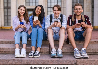 Teenagers with tucked legs in sneakers sit on the stairs in a row and look at the camera cheerfully. Four seniors with smiles are sitting on the steps outdoor the university with phones in hands.