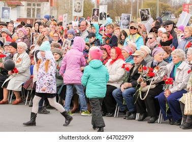 Teenagers and veterans with flowers. Kirishi, Russia - 9 May, 2017. Holding a festive rally dedicated to the Victory Day.