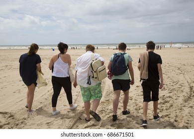 teenagers walking on the beach towards the sea for a swim
