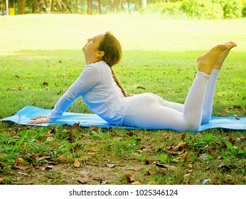 A teenagers  in white dresses are yoga in the park.