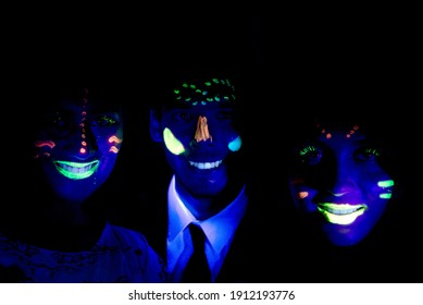 teengers with face painted on glow party with UV light