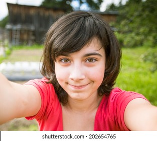 Teen-girl taking a selfie out in the park.