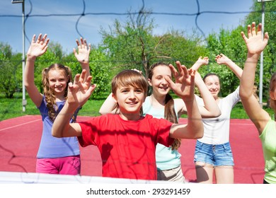 Teens with arms up play volleyball near the net