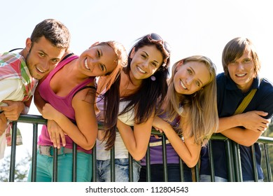 Teens having fun in park leaning fence happy students relaxing