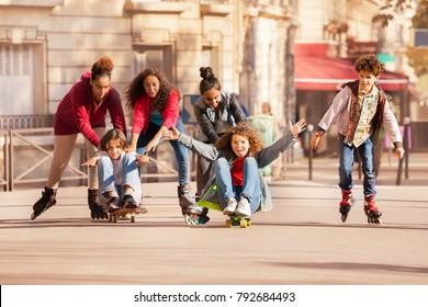 Teens having fun rollerblading and skateboarding