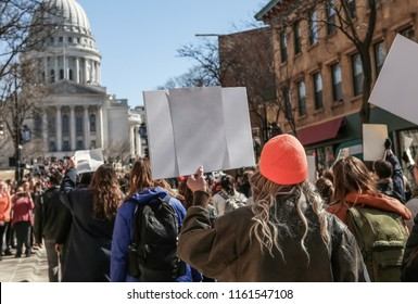 Teens marching to the capitol in protest focus on orange hat