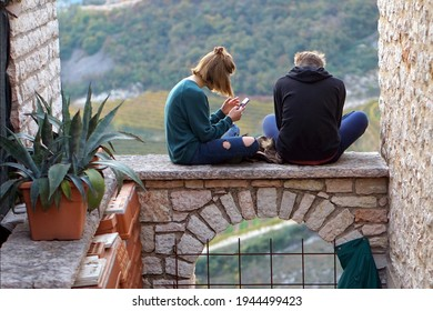 Teens seated on an arch. New technologies and ancient architectures. Teenagers use their mobile phones outdoors.