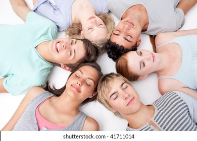 Teens sleeping on floor with heads together in a circle