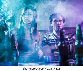 teens smoking marijuana in smoke filled room
