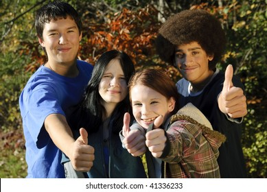 Teens of various ethnic backgrounds outdoors giving a thumbs up. Focus on teen girl second from right.