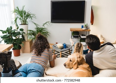 teens watching tv and lying on bed with dog