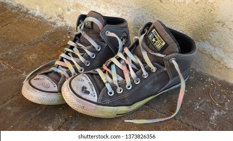 A teen's well-worn, drawn on Converse All-Star sneakers, with the laces painted in rainbow colors for gay pride. Photo taken in Vista, CA / USA on April 18, 2019.