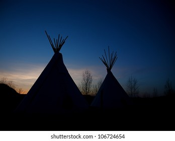 Tee-pees among Birch Trees silhouetted against vignetted blue sky at nightfall