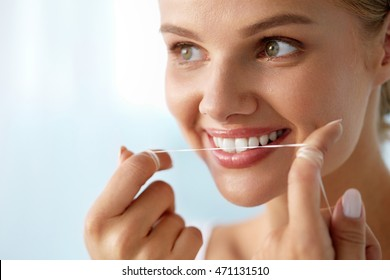 Teeth Care. Closeup Of Beautiful Happy Smiling Woman With Perfect Smile Cleaning Her Healthy White Teeth, Flossing Using Floss. ( Mouth ) Oral Hygiene, Dental Health Concept. High Resolution Image