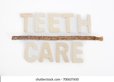 teeth cleaning twig known as  miswak with wooden word TEETH CARE isolated white background