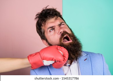 Teeth pain concept. Defenseless head. Suffering. Punch in face. Destroy beauty. Cosmetology and plastic surgery services. Strong punch. Hand in boxing glove punching bearded male face. Painful punch.