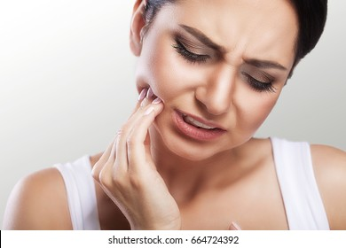 Teeth Problem. Woman Feeling Tooth Pain. Closeup Of A Beautiful Sad Girl Suffering From Strong Tooth Pain. Attractive Female Feeling Painful Toothache. Dental Health And Care Concept.