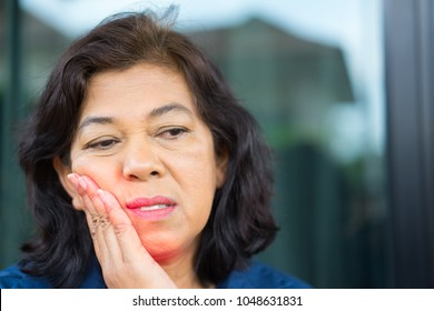 Teeth problem.Asian Senior woman feeling tooth pain.Sad senior woman suffering from strong tooth pain.