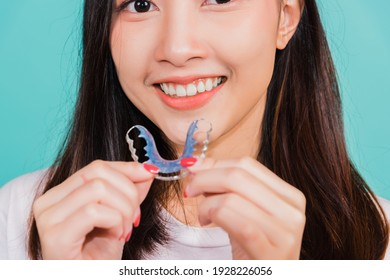 Teeth retaining tools after removable braces, Portrait young Asian beautiful woman smiling holding silicone orthodontic retainers for teeth, Orthodontics dental healthy care concept