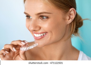 Teeth Whitening. Beautiful Smiling Woman With White Smile, Straight Teeth Using Teeth Whitening Tray. Girl Holding Invisible Braces, Teeth Trainer. Dental Treatment Concept. High Resolution Image