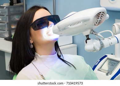 Teeth whitening for woman. Bleaching of the teeth at dentist clinic.
