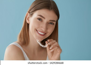 Teeth whitening. Woman with white smile, healthy straight teeth using clear removable braces, invisible teeth tray. Portrait of girl doing dental beauty treatment  - Shutterstock ID 1429284668