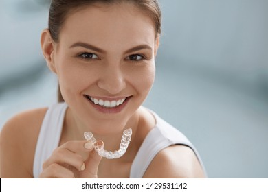 Teeth whitening. Woman with white smile, healthy straight teeth using clear removable braces, invisible teeth tray. Portrait of girl doing dental beauty treatment