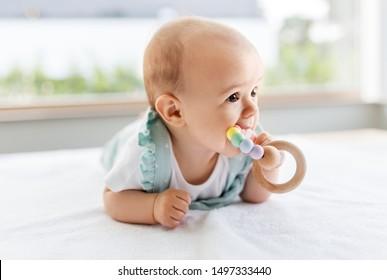 teething, babyhood and people concept - sweet little baby girl lying on white blanket and chewing wooden rattle