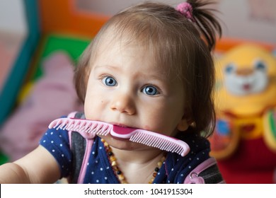 Teething caucasian blonde baby girl playing with a plastic comb in a playard playpen