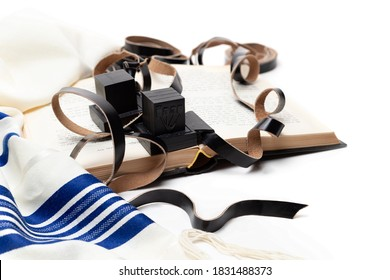Еallith and tefillin and book on white background