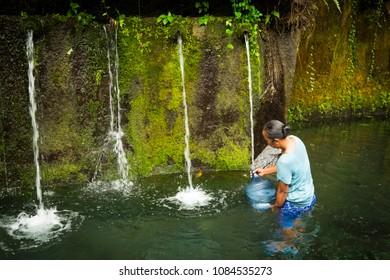 Tegenungan Kemenuh, Bali / Indonesia - December 26 2017: A Balinese woman filling a water gallon under a fountain
