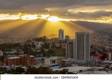 Tegucigalpa, Francisco Morazán/Honduras. January 19 2018. Diagonal sunset light rays coming down over skycrapper in Tegucigalpa, Honduras