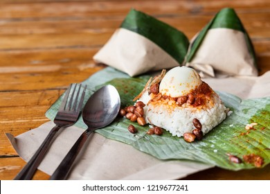 Teh tarik with nasi lemak pack in banana leaf in background, popular breakfast in Malaysia