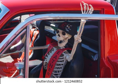 Tehachapi, California USA–October 14, 2018:  Skeleton driver in sporty red pickup truck promises a scary ride at fall apple festival car show.