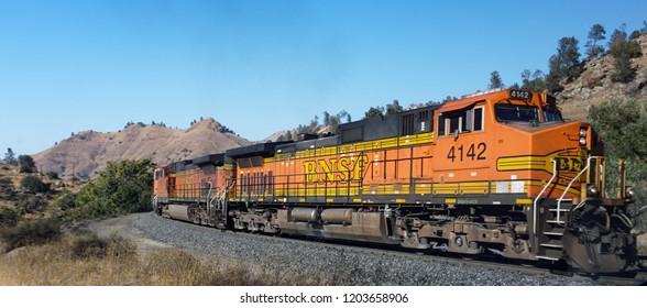 Tehachapi, California USA - October 14, 2018: BNSF railroad locomotives haul a freight train around a bend in the track headed upgrade through the Tehachapi Pass.