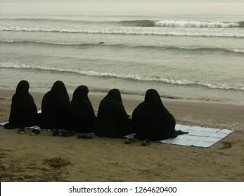 Teheran, Iran / Iran - April 2016: Muslim women sitting at the seaside