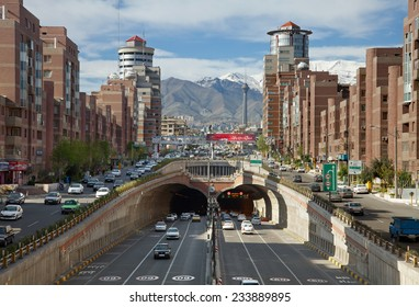 TEHRAN - APR 1: Cars Passing Through Tohid Tunnel with Milad Tower and Alborz Mountains in Background on April 1, 2014 in Tehran, Iran. Tohid Tunnel is the third longest urban tunnel in Middle East.