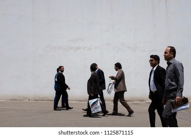 Tehran, Iran – 05 07 2017: A group of Iranian businessman walking behind a white wall in ّIran International Oil Exhibition. Many exhibitions have been held in Tehran international exhibition yearly.
