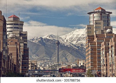 TEHRAN, IRAN - APRIL 1, 2014: Milad Tower and Navvab buildings in front of Alborz Mountains on a clear day. Milad Tower is the second most important landmark of Tehran.