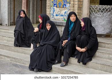Tehran, Iran - April 27, 2017: Iranian women in hijabs are sitting on the steps near the Shrine of Hazrat Abdulazim al-Hasani.