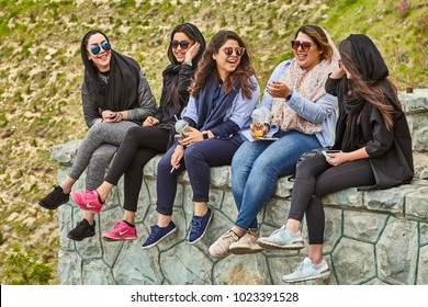 Tehran, Iran - April 28, 2017: Iranian women with cocktails in their hands are sitting in the park, talking to each other and laughing.