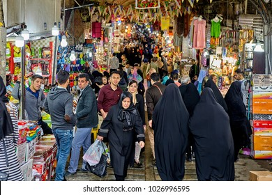 Tehran, Iran - April 29, 2017: Iranian men and women in hijab buy things in a big bazaar.