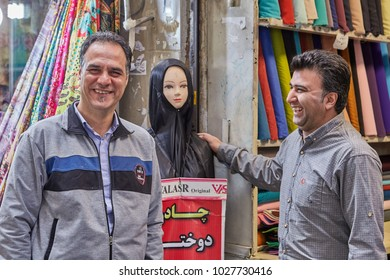 Tehran, Iran - April 29, 2017: Iranian fabric sellers joke about the female dummy in a black religious veil.